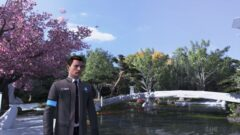 Bryan Dechart wearing a suit and tie standing next to a tree