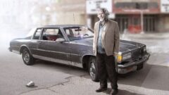 Clancy Brown standing in front of a car