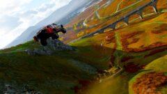 a person flying through the air while riding a snowboard down a river