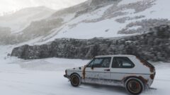 a car parked on the side of a snow covered mountain
