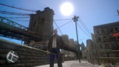 Niko Bellic standing in front of a building with a metal fence