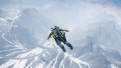 a man riding a snowboard down a snow covered mountain
