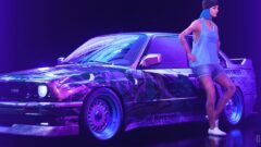 a person sitting on a stage in front of a car