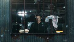 Aidan Gillen standing in front of a window
