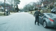 a man standing on a sidewalk next to a car