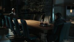 Lance Reddick sitting at a table in a room