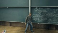 a person standing in front of a blackboard