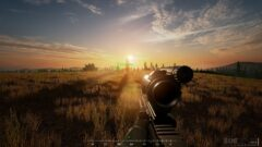 a sunset over a grass field