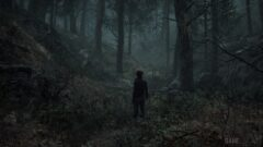 a man standing next to a forest