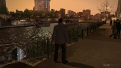 a man standing on a bridge over water with a city in the background
