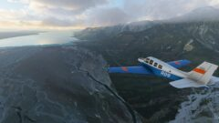 a small airplane flying high up in the air on top of a mountain