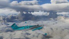 a plane flying through a cloudy blue sky