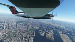 a plane flying over a body of water with a city in the background