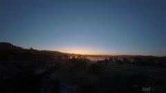 a sunset over a hill